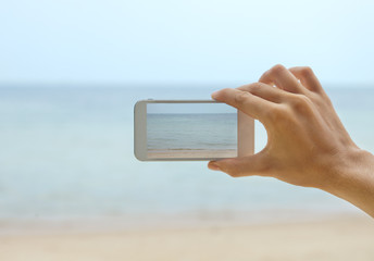hand with telephone - shooting seascape