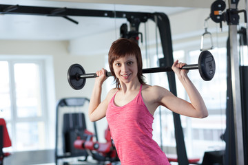 Smiling woman with barbell at the gym