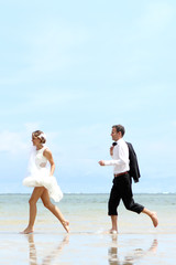 cheerful newlywed couple playfully at the beach