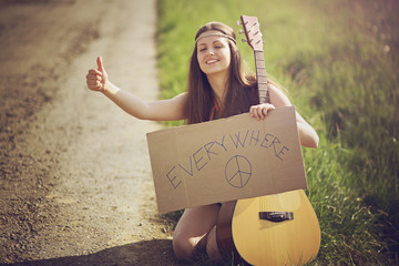 Hippie woman on a country road hitch-hiking