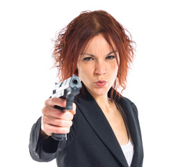 Redhead girl shooting with a pistol