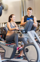 happy woman with trainer on exercise bike in gym