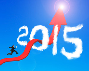 Businessman running arrow upward trend line through 2015 clouds