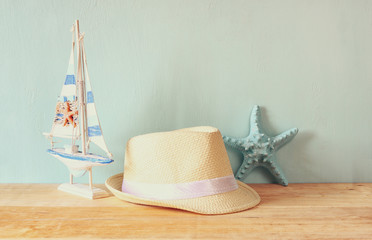 fedora hat, wooden boat and starfish over wooden table