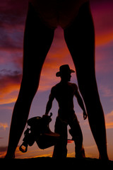 silhouette of a woman in a bikini legs out cowboy with saddle