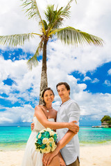Happy groom and bride having fun on the sandy tropical beach und