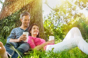 A nice couple sitting in the grass, having a coffee
