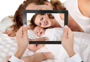 Person Hand Taking Photo Of Mother With Baby