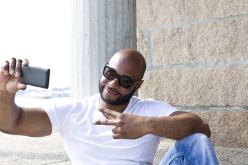 black man with ok symbol and mobile phone