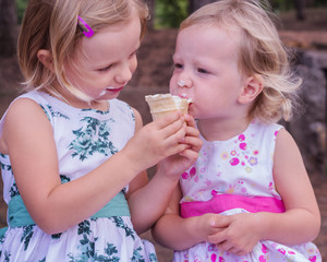 Pretty little girls (sisters) eating ice cream.