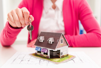 Real estate agent offering keys of new house to buyer