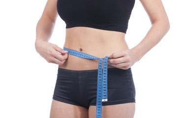Junge Frau mit Maßband misst Bauchumfang