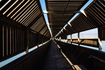 Covered wooden bridge with windows for bird watching