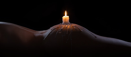 Body scape of a well-shaped woman with burning candle and wax on