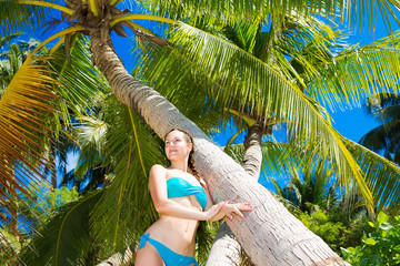 Beautiful young woman in blue bikini relaxes under palm trees.