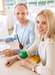 Pretty couple dating moment in cozy sunny restaurant