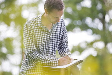 Environmentalist Writing On Notepad In Park