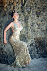 Young beautiful girl in gold dress on the beach of a tropical