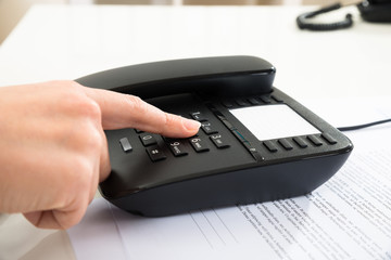 Businessperson Dialing Number On Telephone Keypad