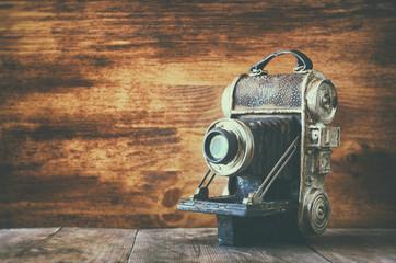 vintage old decorative camera on brown wooden background