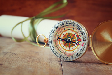 old parchment and antique compass on wooden table