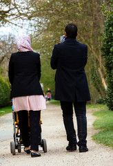 Muslim couple walking with their children in a stroller