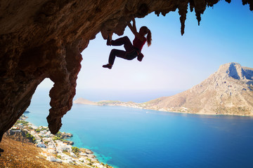 Female rock climber struggling on challenging route on cliff