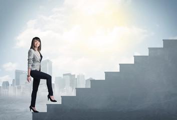 Businesswoman climbing up a concrete staircase concept