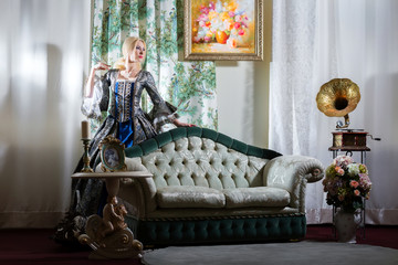 Girl in medieval dress standing next to the sofa