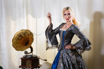 Girl in medieval dress standing next to a gramophone