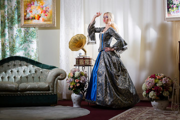 Lady in medieval dress standing next to the sofa