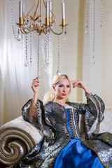 Lady in medieval dress sits on a sofa under the chandelier