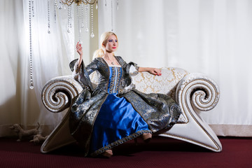 Girl in medieval dress sits on a sofa