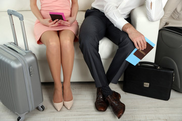 Legs of young happy couple with baggage, sitting on sofa