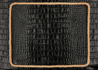 Frame of rope, lies on a background of a black crocodile  leathe