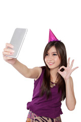 Sweet Asian party girl taking selfie, isolated on white
