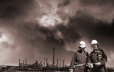 oil workers with refinery in background, dark industrial clouds