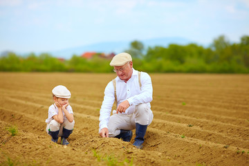 grandpa explaining his grandson the way plants are grow