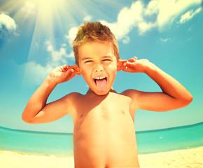 Wall Mural - Summer holidays. Joyful boy having fun at the beach