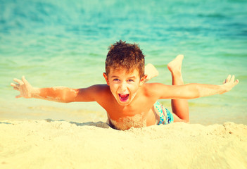 Wall Mural - Summer holidays. Joyful boy having fun at the beach