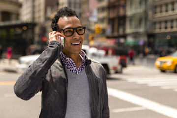 Young African Asian man in New York City talking on cell phone