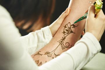 Art of mehndi. Master paints model's leg