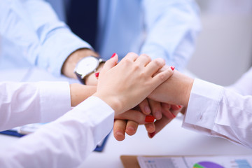Businesspeople holding hands united over meeting table
