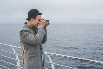 handsome hipster guy taking picture with film camera of the sea
