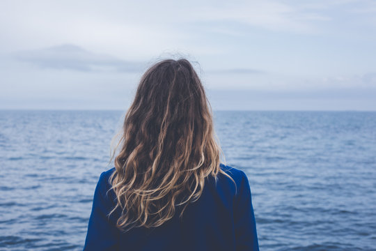 blonde curly girl looking at hazy sunshine calm sea back view