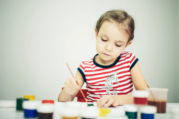little 6 years girl with paint toy