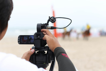 Cameraman working on recording on a beach Polo Tournament