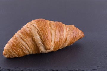 A Close up Image of a Croissant on a Slate Board.