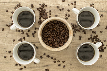 4 Black coffee cup with beans on wooden surface from above