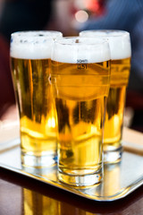 Three glasses of beer on the silver tray